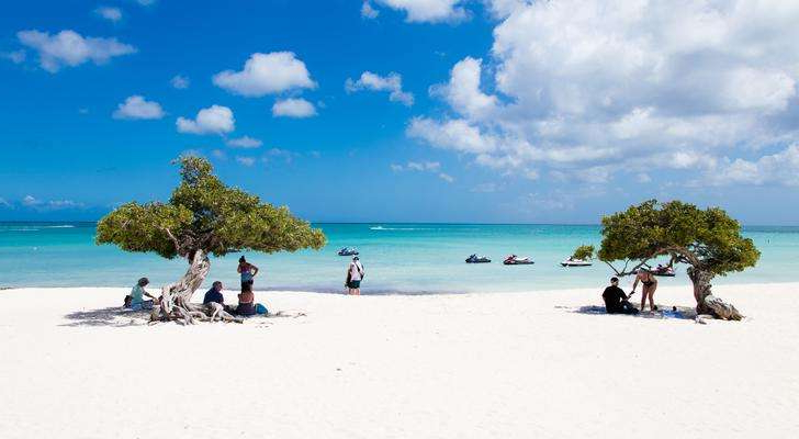 a group of people sitting at a beach: Aruba's Eagle Beach