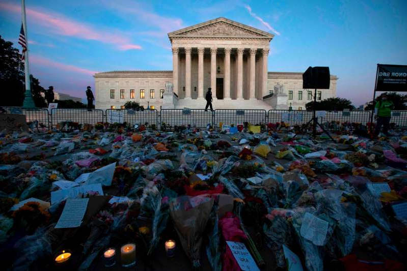 a group of people standing in front of a building: TOPSHOT - Flowers, candles, and signs are pictured at a makeshift memorial outside of the US Supreme Court as people pay their respects to Ruth Bader Ginsburg in Washington, DC on September 19, 2020. - US President Donald Trump vowed to quickly nominate a successor, likely a woman, to replace late Supreme Court Justice Ruth Bader Ginsburg, only a day after the death of the liberal stalwart. (Photo by Jose Luis Magana / AFP) (Photo by JOSE LUIS MAGANA/AFP via Getty Images) ORG XMIT: 0 ORIG FILE ID: AFP_8QC7DU.jpg