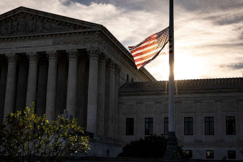 a large clock tower in front of a building: The U.S. flag flies at half staff in front of the Supreme Court building the morning after the death of Justice Ruth Bader Ginsburg.