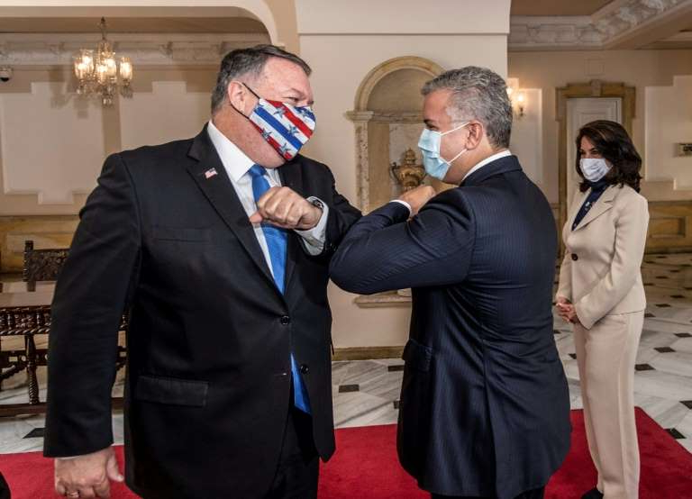 a man wearing a suit and tie talking on a cell phone: Colombian President Ivan Duque (L) and US Secretary of State Mike Pompeo greeting each other with an elbow bump at Narino Presidential Palace in Bogota