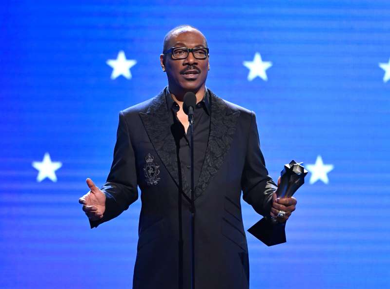 Eddie Murphy wearing a suit and tie: SANTA MONICA, CALIFORNIA - JANUARY 12: Eddie Murphy accepts the Lifetime Achievement Award onstage during the 25th Annual Critics' Choice Awards at Barker Hangar on January 12, 2020 in Santa Monica, California. (Photo by Amy Sussman/Getty Images)