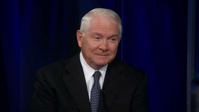 Robert Gates wearing a suit and tie standing in front of a curtain
