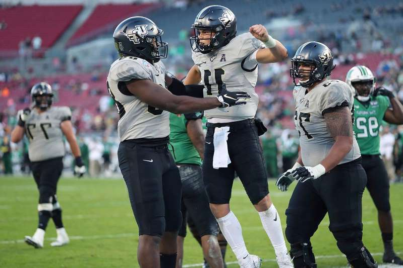 a group of baseball players standing on top of a grass covered field: Central Florida quarterback Dillon Gabriel (11) celebrates after a touchdown against Marshall during the Gasparilla Bowl NCAA college football game Monday, Dec. 23, 2019, in Tampa, Fla. (Stephen M. Dowell/Orlando Sentinel via AP)