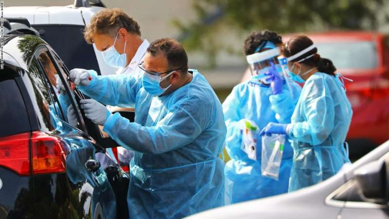 a man and a woman in a car: A medical professional administers a Covid-19 test at a free testing site at the Endicott Estate in Dedham, Massachusetts on September 14, 2020. Fallon Ambulance is conducting the testing during the continuing coronavirus pandemic. (Photo by Pat Greenhouse/The Boston Globe via Getty Images)