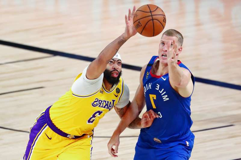 a man holding a football ball: Mason Plumlee (left) is getting roasted for his lack of defense on Anthony Davis Sunday night.