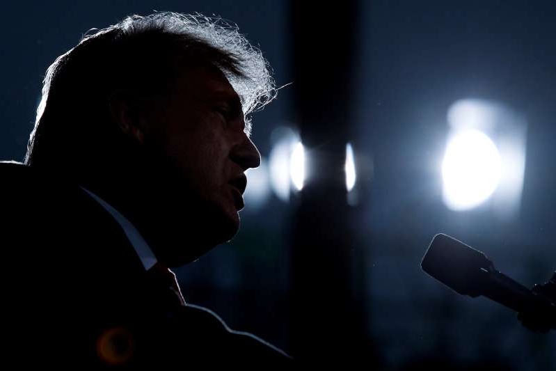 a man in a dark room: U.S. President Donald Trump attends a campaign event in Fayetteville