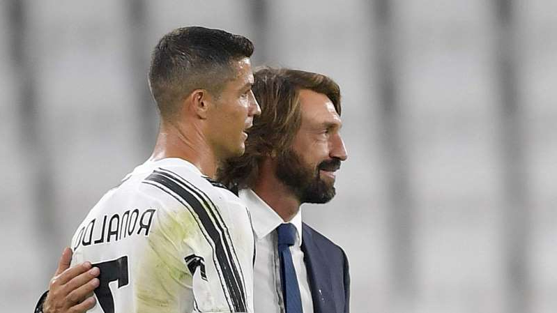 a man wearing a suit and tie: Andrea Pirlo and Cristiano Ronaldo after Juventus' win over Sampdoria