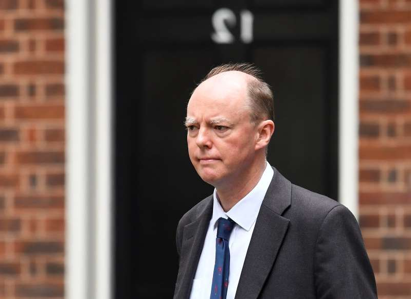 a man wearing a suit and tie standing in front of a building: Chief Medical Officer for England Chris Whitty is seen outside Downing Street in London