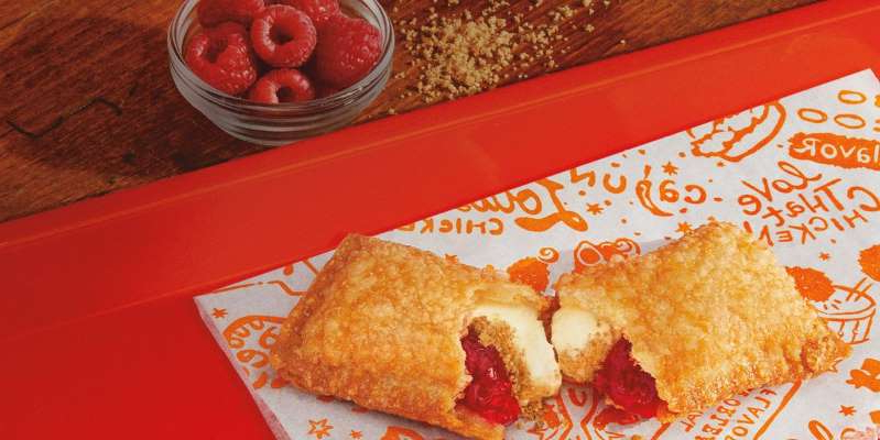 a plate of food with a slice of cake on a table: Popeyes has launched a new limited time offer, the raspberry cheesecake pie, after the success of the strawberry cheesecake pie earlier this year.