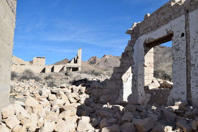 a stone building that has a rocky cliff: Ruins in the ghost town of Rhyolite, Nevada