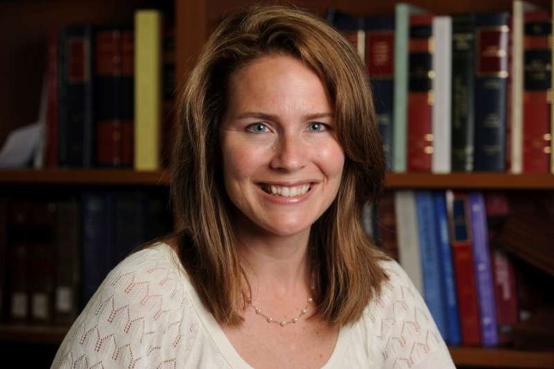 a woman holding a book shelf: FILE PHOTO: Judge Amy Coney Barrett poses in an undated photograph obtained from Notre Dame University