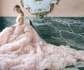 a woman sitting on a bed: On the 21st of September, ELLE will host the annual ELLE International Bridal Awards for 2020, revealing the best in bridal for the year.