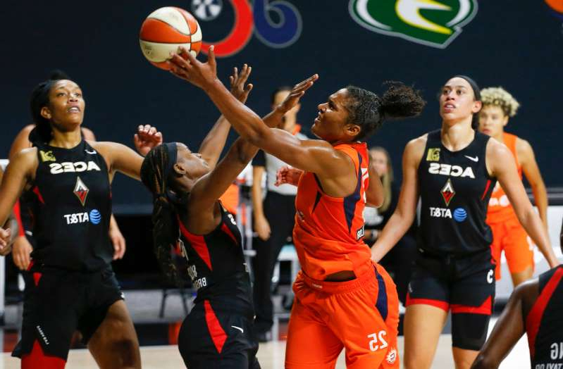 Dearica Hamby et al. playing a game of football: Connecticut Sun forward Alyssa Thomas shoots over Las Vegas Aces guard Sugar Rodgers during Sunday's WNBA playoff game in Palmetto, Florida.