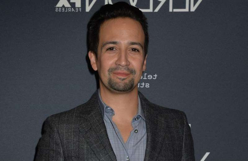 Lin-Manuel Miranda wearing a suit and tie smiling at the camera