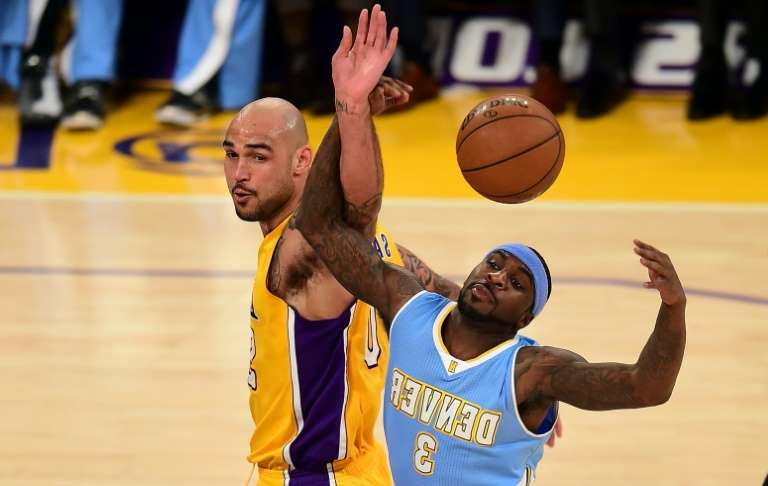 Robert Sacre holding a basketball: Ty Lawson (L) used to play for the Denver Nuggets in the NBA