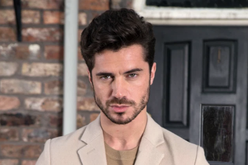 Sam Robertson standing in front of a building: Coronation Street actor Sam Robertson plays Adam Barlow on the soap