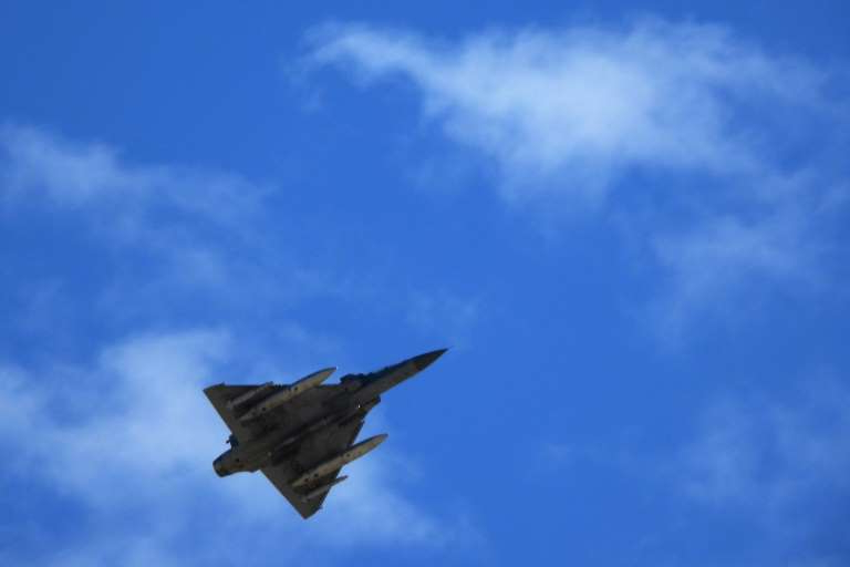 a fighter jet flying through a blue sky: An Indian Air Force fighter jet flies over Leh, the joint capital of the union territory of Ladakh bordering China