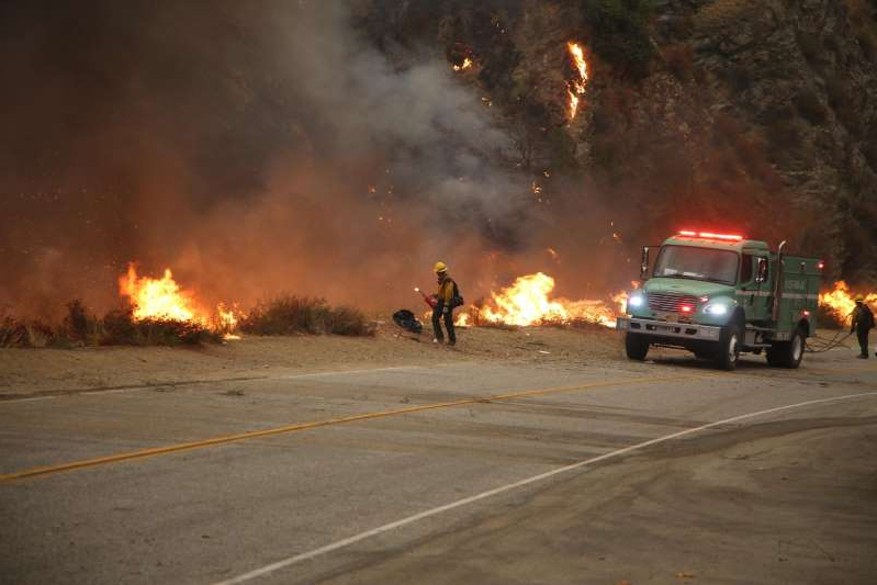 a fire truck that is driving down the road: Firefighters set a prescribed burn ahead of the Bobcat Fire.