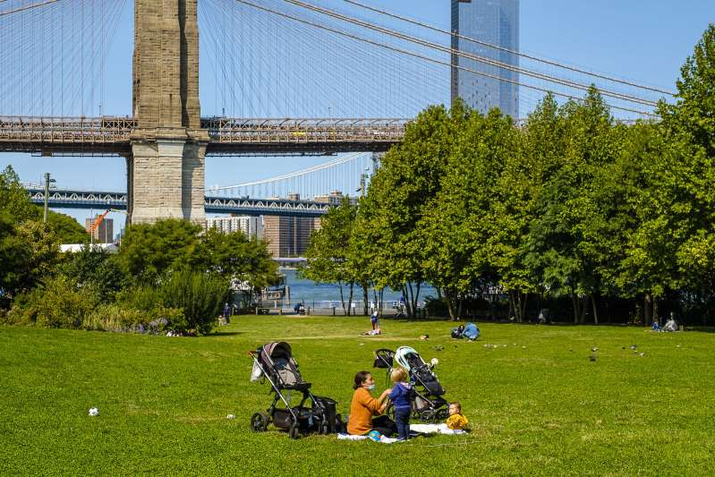 a group of people standing on a lush green field: New Yorkers enjoy the beautiful weather at Brooklyn Bridge Park as the DOJ declares NYC to be an anarchist city, Monday, Sep. 21, 2020. (Jeff Bachner/New York Daily News)