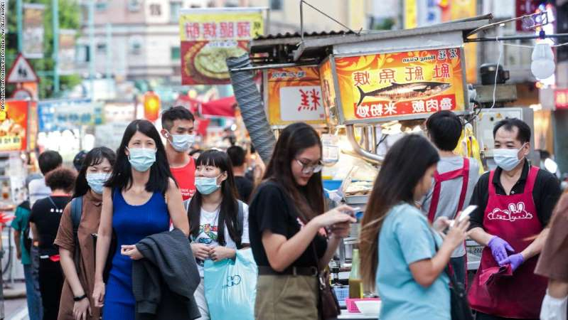 a group of people walking down a street: People wearing protective masks walk past food stalls at the Ningxia Night Market in Taipei, Taiwan, on July 30, 2020.