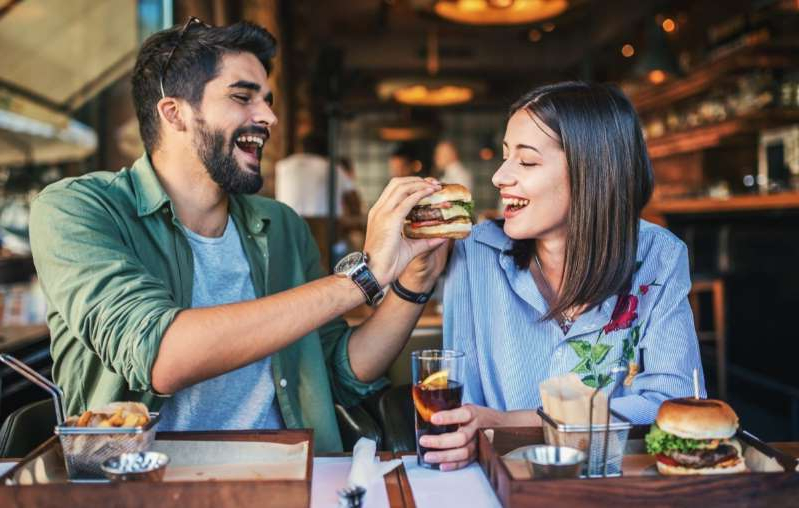 a man sitting at a table eating food: Young couple eating burgers