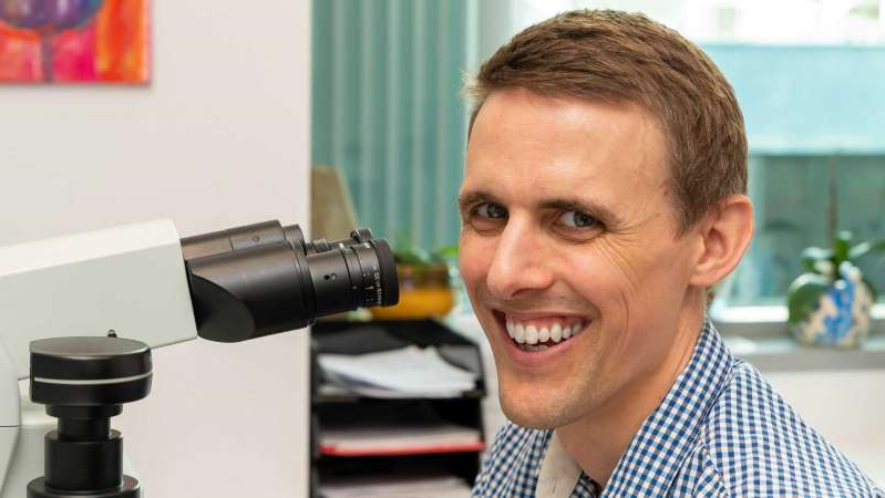 a man smiling for the camera: Microbiologist Dr Evan Bursle said the coronavirus pandemic has been a unique challenge in his career. (Supplied: Sullivan Nicolaides Pathology)