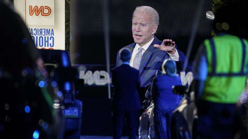 a man standing on a stage: Audience members listen as Democratic presidential nominee Joe Biden participates in a CNN town hall event on September 17 in Moosic, Pennsylvania.