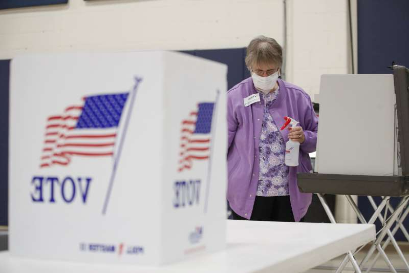 a man wearing a suit and tie: An election observer cleans voting booths during a Democratic presidential primary election at the Kenosha Bible Church gym in Kenosha, Wisconsin, on April 7, 2020. Some states do not allow online registration to vote.