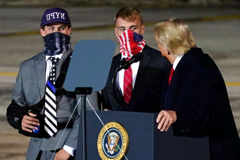 a person wearing a suit and tie: President Donald Trump brings two football players from Little Miami High School who were suspended for a short time for carrying flags that showed support for law enforcement at the start of a game on Sept. 11, onto stage as he speaks during a campaign rally at Eugene F. Kranz Toledo Express Airport, Monday, Sept. 21, 2020, in Swanton, Ohio. (AP Photo/Alex Brandon)