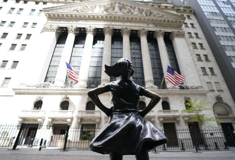 a statue in front of a building: 'Fearless Girl' has become a powerful monument to female empowerment.