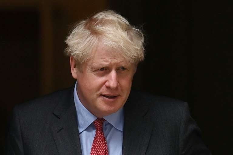 Boris Johnson wearing a suit and tie: Britain's Prime Minister Boris Johnson responded to criticism that the UK's contact tracing and testing programme is not working well enough in the face of a surge in cases of Covid-19