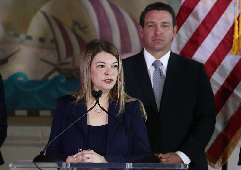 Ron DeSantis wearing a suit and tie: Judge Barbara Lagoa speaks as Florida Governor Ron DeSantis looks on during a press conference in Miami, Florida on January 9, 2019.