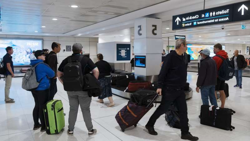 a group of people waiting for their luggage at an airport: Passengers arriving from Adelaide into Sydney.