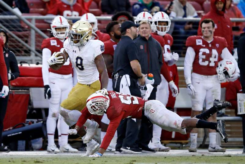 a group of people watching a baseball game: Notre Dame running back Jafar Armstrong (8) eludes Stanford's Obi Eboh during the fourth quarter of their 2019 game at Stanford Stadium.