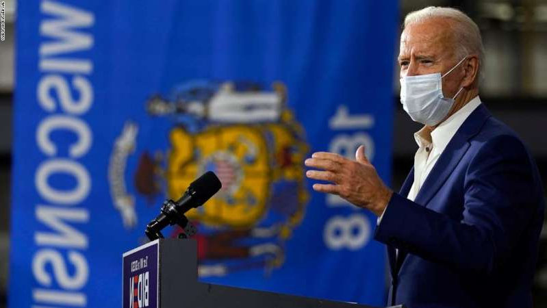 a man holding a sign: Democratic presidential candidate former Vice President Joe Biden speaks at Wisconsin Aluminum Foundry in Manitowoc, Wis., Monday, Sept. 21, 2020.