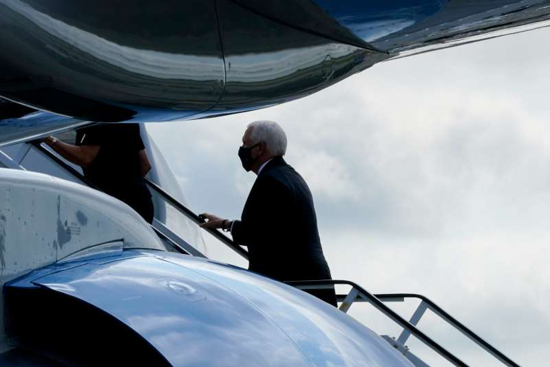 a man sitting on a boat: Vice President Mike Pence boards Air Force Two after attending a ceremony marking the 19th anniversary of the 9/11 terrorist attacks at the National September 11 Memorial & Museum, Friday, Sept. 11, 2020, in New York. (AP Photo/Mary Altaffer) ORG XMIT: NYMA105