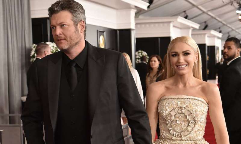 a man standing in front of Gwen Stefani, Blake Shelton posing for the camera: Hello! Magazine