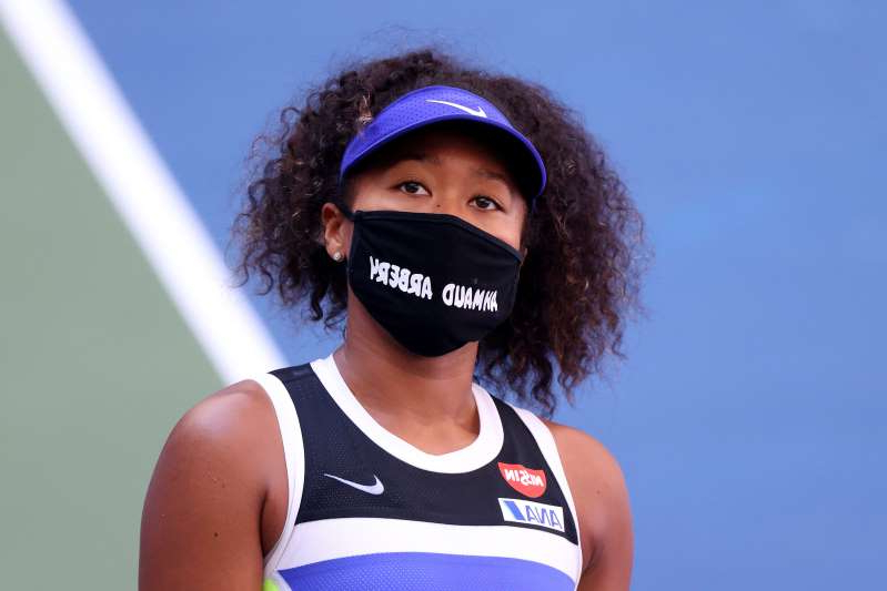 a woman wearing a blue shirt: Naomi Osaka of Japan wears a protective face mask with the name, Ahmaud Arbery stenciled on it at the 2020 U.S. Open at USTA Billie Jean King National Tennis Center on September 04, 2020 in New York City. Ahmaud Arbery, an unarmed 25-year-old African-American man, was pursued and fatally shot while jogging in Glynn County, Georgia.