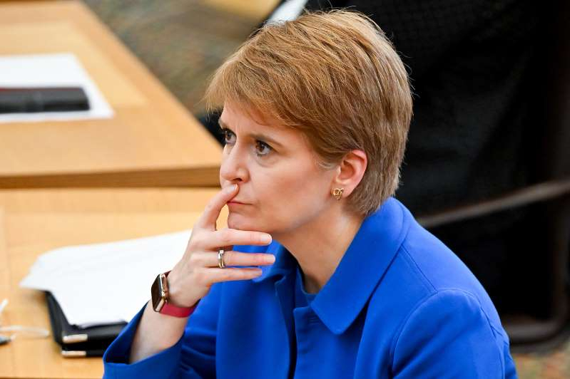 a young man sitting at a table: Nicola Sturgeon defended the introduction of tougher coronavirus restrictions in Scotland. (Jeff J Mitchell/PA)