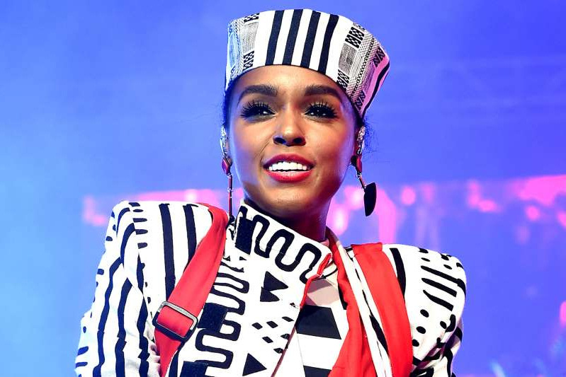 Janelle Monae wearing a costume and holding a sign posing for the camera: