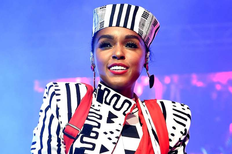 Janelle Monae wearing a costume and holding a sign posing for the camera: Kevin Winter/Getty