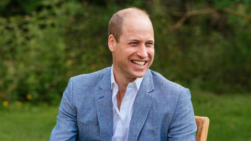 Prince William, Duke of Cambridge wearing a suit and tie smiling at the camera