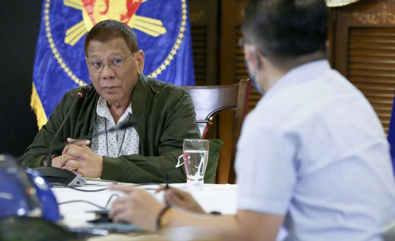 Rodrigo Duterte et al. sitting at a table using a laptop