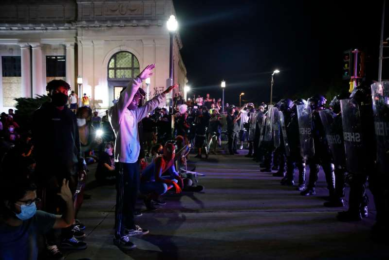 "a group of people standing in front of a crowd: Protestors face off with police outside the County Courthouse during demonstrations against the shooting of Jacob Blake in Kenosha, Wisconsin on August 25, 2020. Facebook has been accused in a lawsuit of ""shirking"" its responsibility to remove pages which promoted violence ahead of the deadly Kenosha protests."