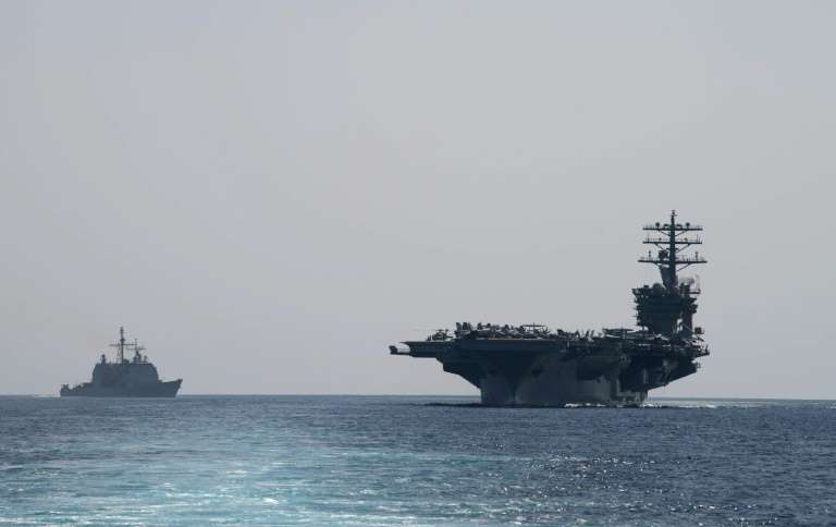 a large ship in a body of water: A US aircraft carrier through the Strait of Hormuz on Friday after Washington threatened to enforce