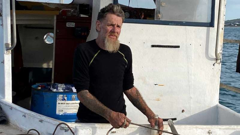 a man standing on top of a cutting board: Tony Higgins on board his boat Margrel at Granite Island. (ABC News: Sarah Mullins)