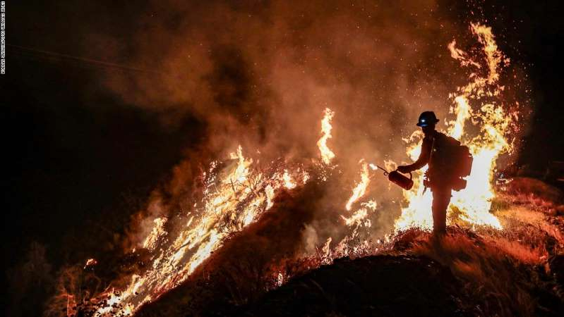a man with a mountain in the dark: Angeles National Forest, CA, Tuesday, September 22, 2020 - Firefighters continue to battle the Bobcat Fire North of Mt. Wilson along Angeles Crest Highway.