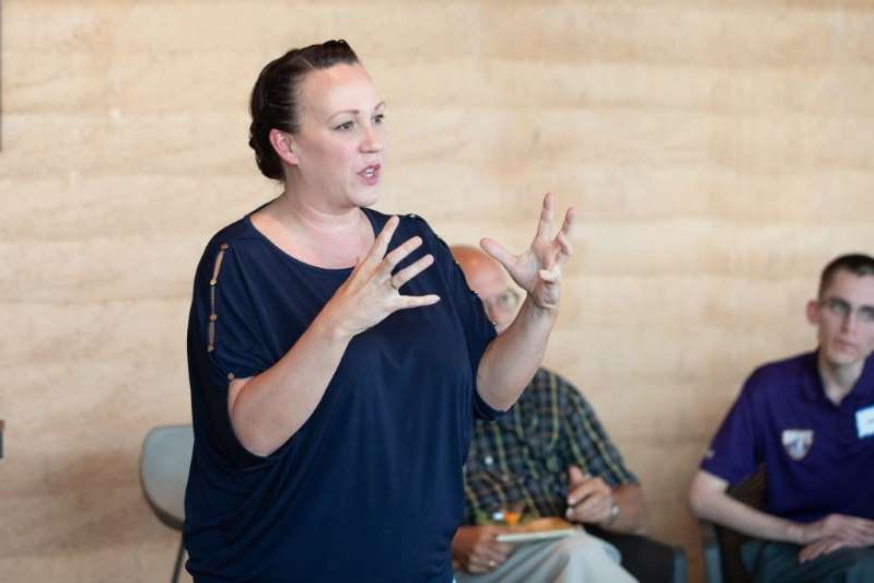 MJ Hegar et al. posing for the camera: M.J. Hegar speaks to voters at an event on September 15, 2018 at The Den at Wolf Ranch in Georgetown, Texas
