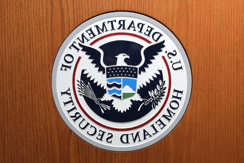 a close up of a logo on a wooden table: The Department of Homeland Security seal