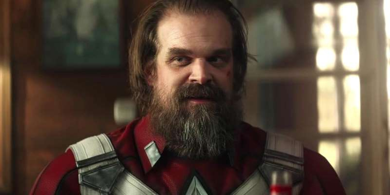 a close up of David Harbour with a beard looking at the camera: Black Widow star David Harbour has reacted to Disney delaying the movie until next spring.